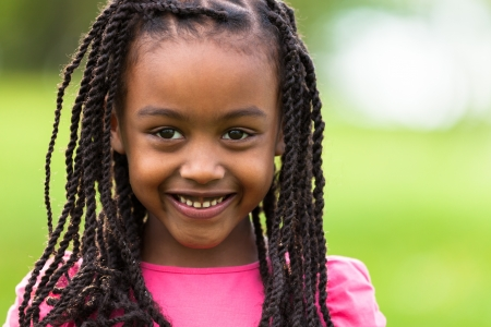 braids: Outdoor close up portrait of a cute young black girl smiling - African people Stock Photo