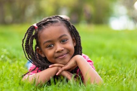 girl lying down: Retrato al aire libre de una ni�a de negro linda joven tendido en la hierba y sonriendo - pueblo africano Foto de archivo