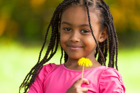 Outdoor portrait of a cute young black girl holding a dandelion flower - African people photo