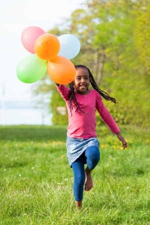 Outdoor portrait of a cute young  little black girl playing with balloons - African people photo