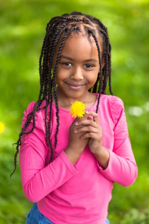 braided: Outdoor portrait of a cute young black girl holding a dandelion flower - African people Stock Photo