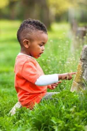 diversity children: Outdoor portrait of a cute young  little black boy playing outside - African people