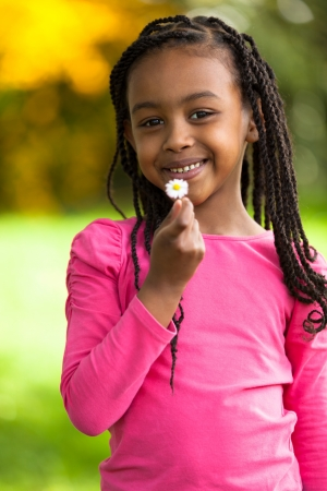 braids: Outdoor portrait of a cute young black girl holding a dandelion flower - African people Stock Photo