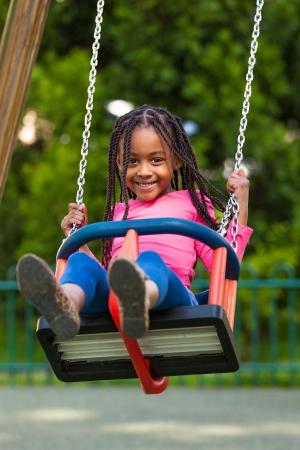 children playground: Retrato al aire libre de una muchacha joven negro lindo que juega con un columpio - pueblo africano Foto de archivo