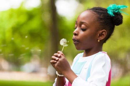blowing dandelion: Outdoor ritratto di una cute giovane ragazza nera che soffia un fiore di tarassaco - popolo africano