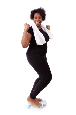 weight loss success: African American woman cheering on scale isolated over white background - African people