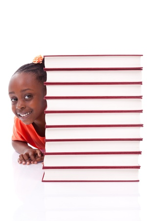 Cute black african american little girl hidden behind a stack of books, isolated on white background - African people - Children photo