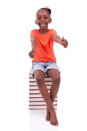 Cute black african american little girl seated in a stack of books making thumbs up, isolated on white background - African people - Children Stock Photo - 19665304