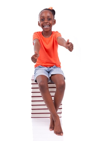 Cute black african american little girl seated in a stack of books making thumbs up, isolated on white background - African people - Children Stock Photo - 19665290