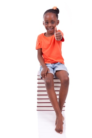 Cute black african american little girl seated in a stack of books making thumbs up, isolated on white background - African people - Children Stock Photo - 19665269