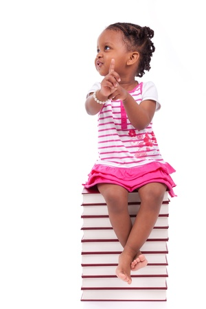 Cute black african american little girl seated in a stack of books, isolated on white background - African people - Children Stock Photo - 19665315