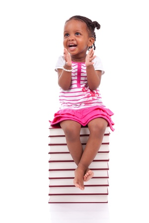 Cute black african american little girl seated in a stack of books, isolated on white background - African people - Children Stock Photo - 19665280