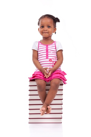 Cute black african american little girl seated in a stack of books, isolated on white background - African people - Children Stock Photo - 19665263