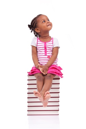 african education: Cute black african american little girl seated in a stack of books, isolated on white background - African people - Children Stock Photo