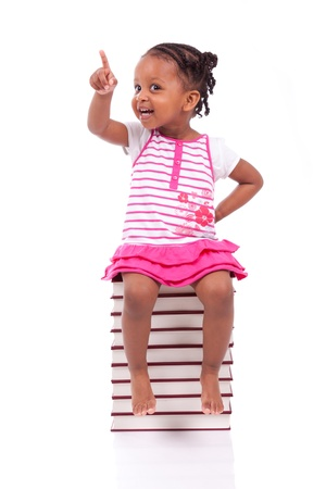 preschool: Cute black african american little girl seated in a stack of books, isolated on white background - African people - Children Stock Photo