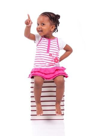 kinder: Lindo negro Ni?el afroamericano sentado en una pila de libros, aislados en fondo blanco - los africanos - Ni?