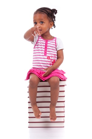 Cute black african american little girl seated in a stack of books, isolated on white background - African people - Children Stock Photo - 19665265