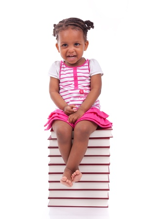Cute black african american little girl seated in a stack of books, isolated on white background - African people - Children photo