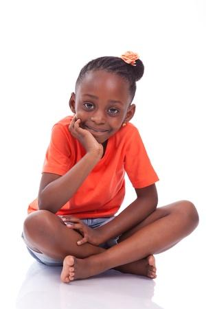 Schattig klein Afrikaans Amerikaans meisje zitten op de vloer - Zwarte kinderen, geïsoleerd op witte achtergrond