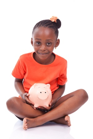 american money: Cute little black girl holding a smiling piggy bank, isolated on white background - African children