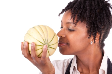 caribbean food: Young happy black   african american woman smelling a fresh melon isolated on white background