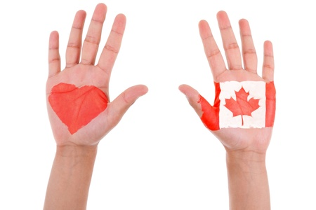 i love canada: Hands with a painted heart and canadian flag, i love canada concept, isolated on white background Stock Photo