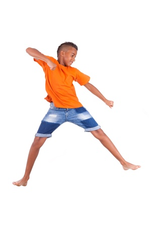 Portrait of a cute teenage black boy jumping over white background - African people Stock Photo - 21307799