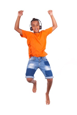 playing music: Portrait of a cute teenage black boy jumping over white background - African people Stock Photo