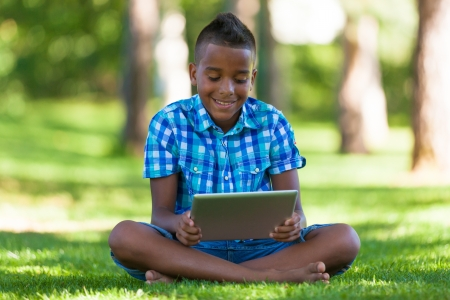 Outdoor portrait of student black boy using a tactile tablet - African people photo