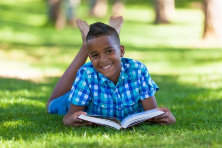 Outdoor portrait of student black boy reading a book - African people Stock Photo - 21294343