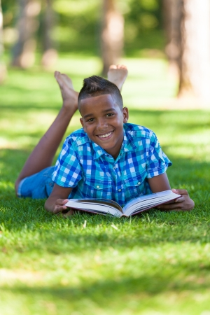 Outdoor portrait of student black boy reading a book - African people Stock Photo - 21294348