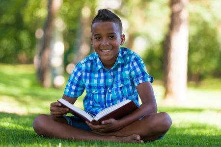 r boy: Retrato al aire libre del estudiante niño negro leyendo un libro - los africanos Foto de archivo