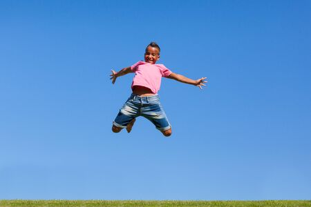 Outdoor portrait of a cute teenage black boy jumping over a blue sky - African people Stock Photo - 21307817
