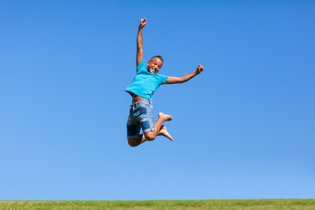 Outdoor portrait of a cute teenage black boy jumping over a blue sky - African people Stock Photo - 21307818