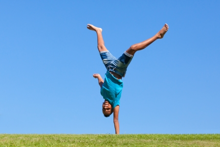 Outdoor portrait of a cute teenage black boy jumping over a blue sky - African people photo