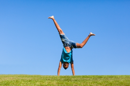 Outdoor portrait of a cute teenage black boy jumping over a blue sky - African people Stock Photo - 21307820