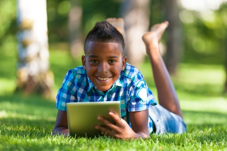 Outdoor portrait of student black boy using a tactile tablet - African people Stock Photo - 21307821