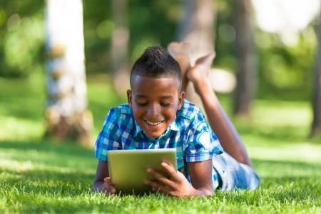 garcon africain: Outdoor portrait d'étudiant garçon noir en utilisant une tablette tactile - Africains Banque d'images