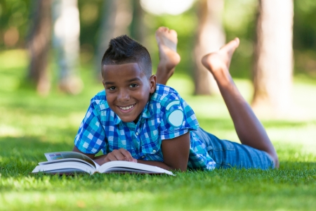 Outdoor portrait of student black boy reading a book - African people photo
