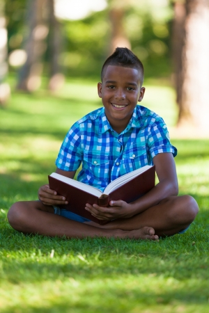 Outdoor portrait of student black boy reading a book - African people Stock Photo - 21307824