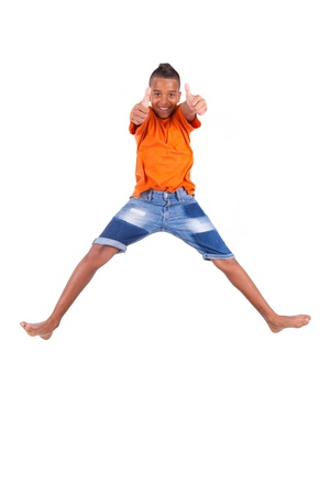 Portrait of a cute teenage black boy jumping over white background - African people photo