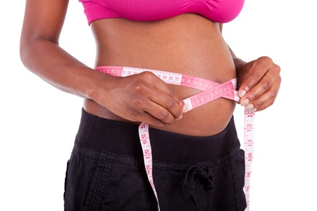Young pregnant black woman measuring her belly, isolated on white background - African people photo