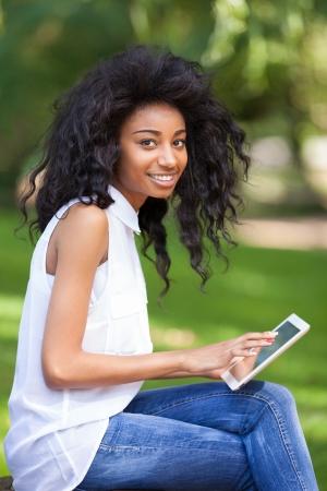 笑みを浮かべて 10 代黒の少女の触覚タブレット - アフリカの人々 を使用して屋外のポートレート 写真素材