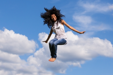 lady fly: Outdoor portrait of a smiling teenage black girl jumping over a blue sky - African people Stock Photo