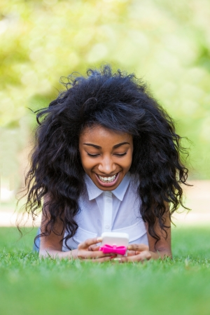 Smiling teenage black girl using a phone, lying down on the grass - African people Stock Photo - 21431207