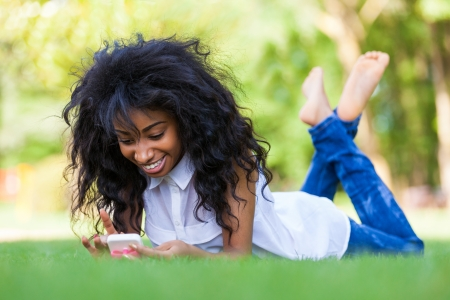 texting: Smiling teenage black girl using a phone, lying down on the grass - African people Stock Photo