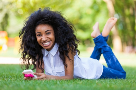 Smiling teenage black girl using a phone, lying down on the grass - African people Stock Photo - 21431208