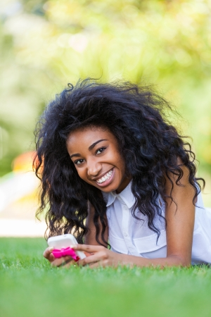 Smiling teenage black girl using a phone, lying down on the grass - African people Stock Photo - 21431209
