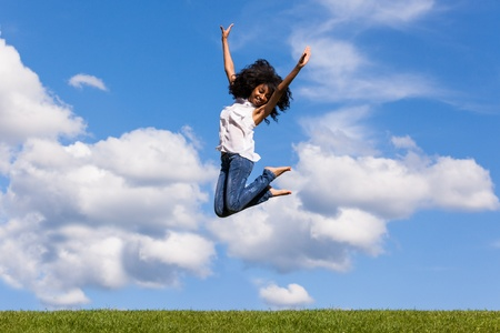 african: Outdoor portrait of a smiling teenage black girl jumping over a blue sky - African people Stock Photo