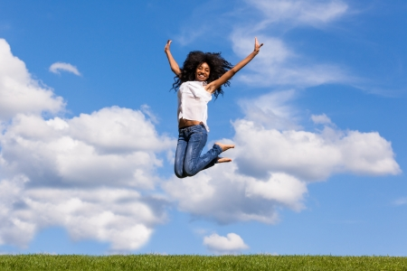 Outdoor portrait of a smiling teenage black girl jumping over a blue sky - African people photo